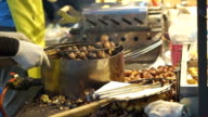 Seller grilling squid and peeling roasted chestnut on street food stall. Autumn food of Asia video