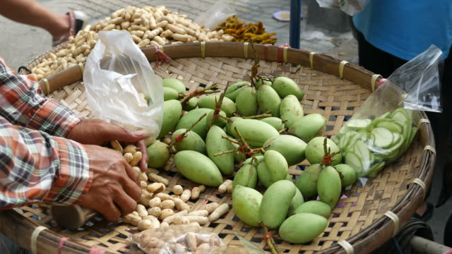Selling boiled peanuts and mangoes, street food, Thailand video