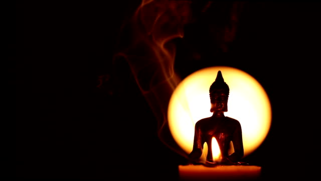 semi silhouette of Buddha statue with one candle and moving incense smoke and copy space video