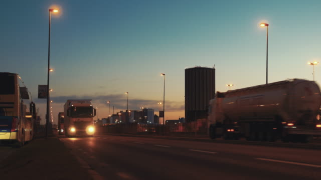 Semi trailer trucks and tanker trucks traffic passing by on street at dusk. Logistics transportation, container terminal in the background video