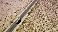 Semi truck driving on highway through desert video