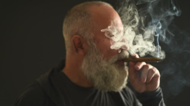 Senior Adult handsome man smoking a cigar on a gray background. video