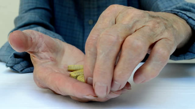 Senior adult holding a medicine pill in his hands. video