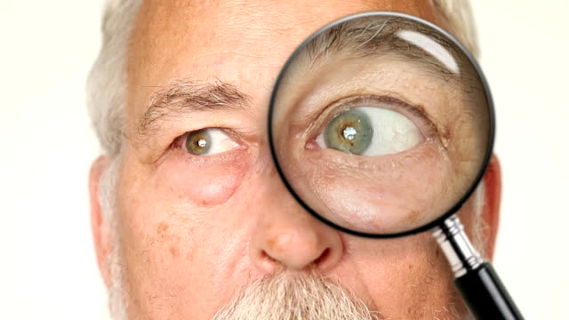Senior Adult Male Looking Through Magnifying Glass video