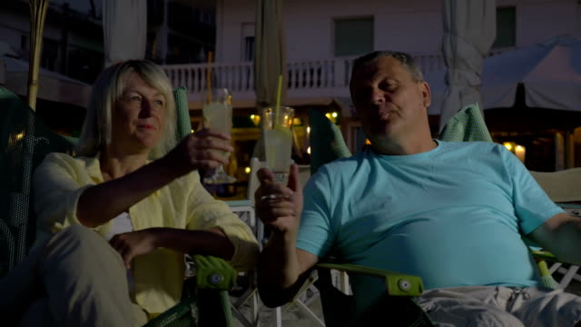Senior adult man and woman drinking cocktails video
