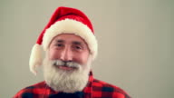 Senior adult man looking into the camera and smiling Santa Claus hat on a gray background. slow motion video