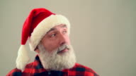 Senior adult man nods his head and smiling Santa Claus hat on a gray background. video