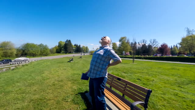 Senior adult man reading on a bench with back pain video