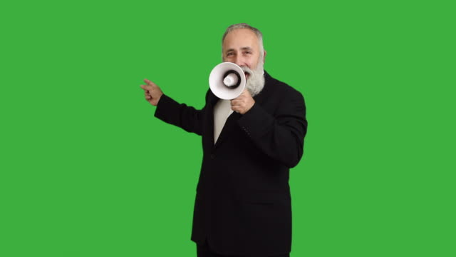 Senior adult man speaks into a megaphone on a green background video