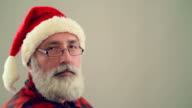 Senior adult man winking and smiling Santa Claus hat on a gray background. video