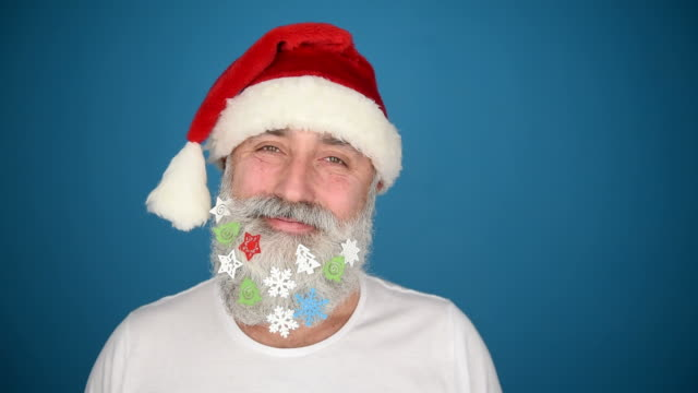 Senior adult man with a beard in elegant hat of Santa Claus on a blue background video