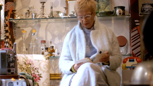 Senior adult woman browsing in antiques store video