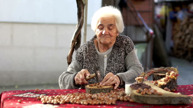 senior adult woman cracking hazelnut with hammer video