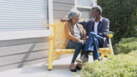 Senior African American couple chatting on bench video