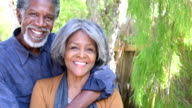 Senior African American couple embracing, looking towards camera video
