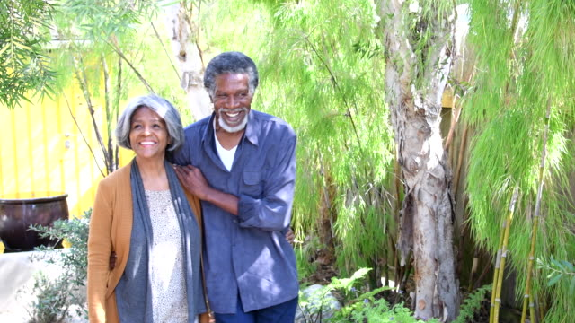 Senior African American couple in garden, woman touching tree video