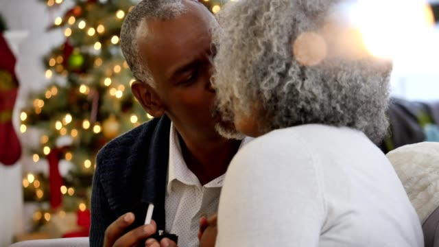 Senior African American couple kissing after exchanging Christmas gifts video