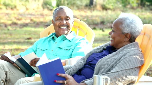 Senior African American couple outdoors reading, talking video