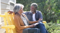 Senior African American couple sitting on chairs outside, laughing video