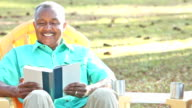 Senior African American couple sitting outdoors, reading video