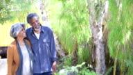Senior African American couple walking in garden, smiling video