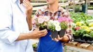 Senior African American garden center customer shops for spring flowers video