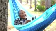 Senior African American man reading in hammock video