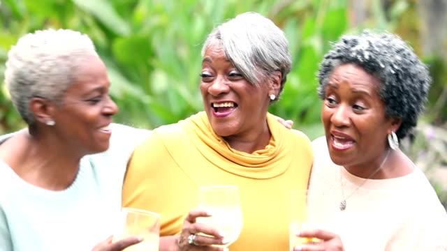 Senior African American woman conversing, drinking video