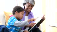 Senior African American woman showing book to grandson, smiling video