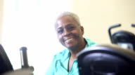 Senior African American woman working out in gym on exercise bike video
