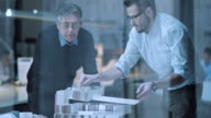 DS Senior and younger architect discussing architectural model details video