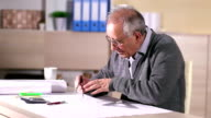 Senior architect working on construction blueprint in office video