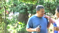 Senior Asian couple with water bottle in park video