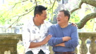 Senior Asian man and adult son talking, laughing in park video