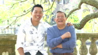 Senior Asian man and adult son talking, smiling in park video