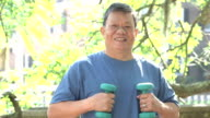 Senior Asian man exercising in park with hand weights video