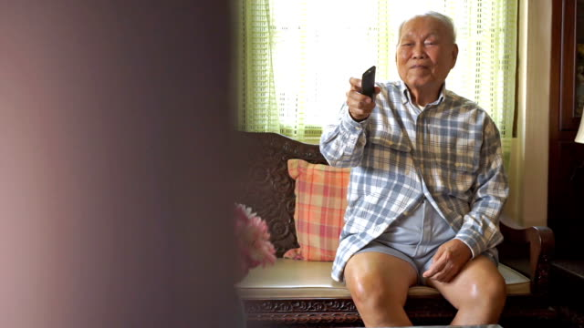 Senior Asian Man watching television and use remote video