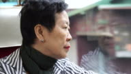 Senior Asian woman sitting on train and looking out through window. Thinking and enjoying view during retirement trip video