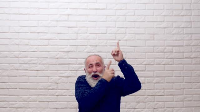 senior beard man showing an copy space video