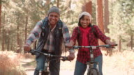 Senior black couple sitting on bikes in a forest, close up video