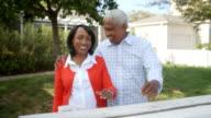 Senior black couple walk into focus outside their home video