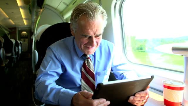 Senior Businessman Commuting On Train Using Digital Tablet video