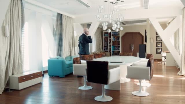 Senior businessman speaks by phone in hotel video