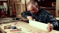 Senior carpenter sending piece of timber with sandpaper video