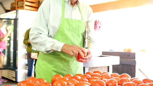 Senior Caucasian grocer examines tomatoes at produce market video
