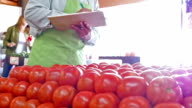 Senior Caucasian grocer taking inventory of tomatoes at produce market video
