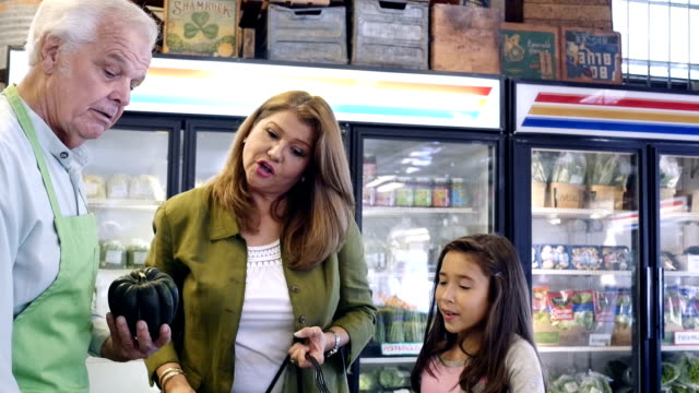Senior Caucasian produce clerk explaining difference between squash to Hispanic mother and daughter video