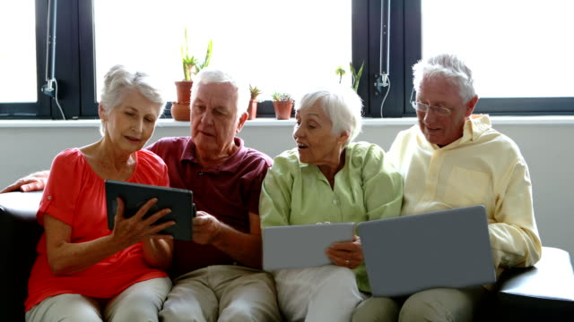 Senior citizens using digital tablet, mobile phone and laptop video