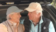 Senior couple at back of car before hiking, close up shot video