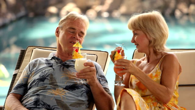 Senior couple at tropical resort have cocktails by the pool video